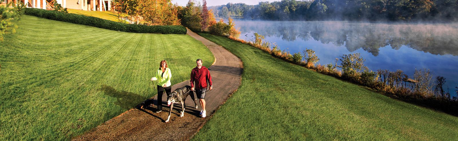 Couple walking dog along lakeside trail in Sterling on the Lake