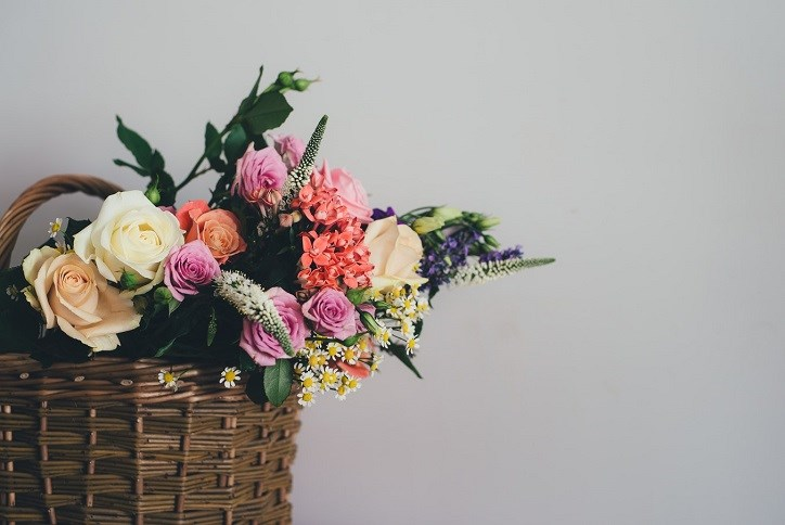 Assortment of different colored spring flowers in a basket with grey backdrop.