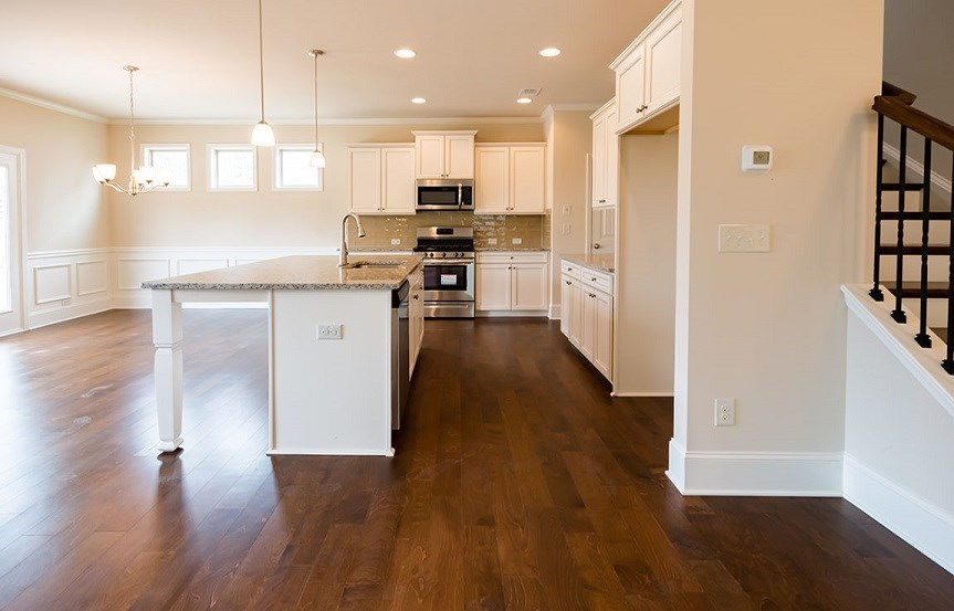 View of the kitchen with an island and wood floors.