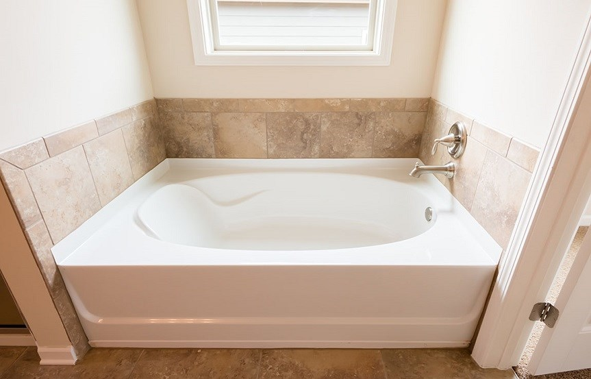 White bathtub with stone backsplash.