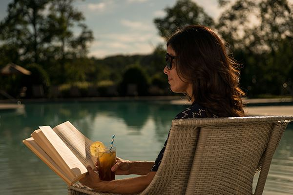 Woman relaxing and reading poolside in Sterling on the Lake.
