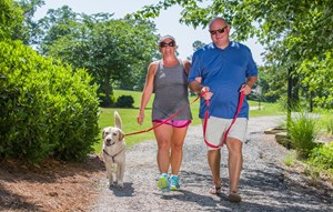 couple-walking-dog-on-trail.jpg