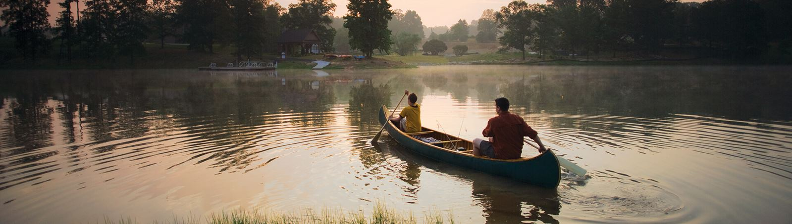 Father and son canoeing at dawn on Lake Sterling