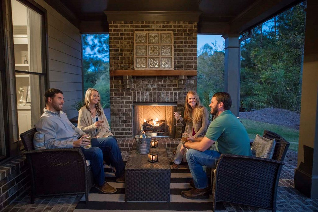 Two couples sitting on the covered back porch by a fire.