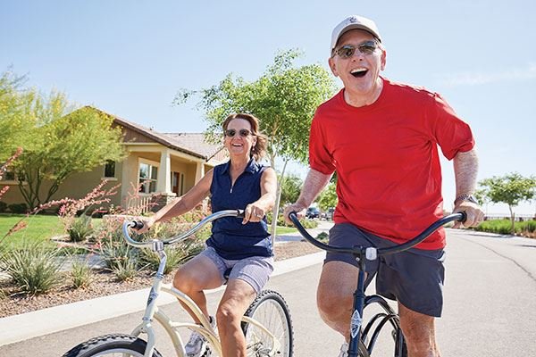 Active adult couple riding bicycles. Encore, by David Weekley in Sterling on the Lake.