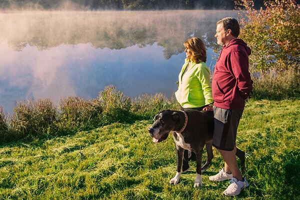 Couple and their dog on lakeside trail in Sterling on the Lake.