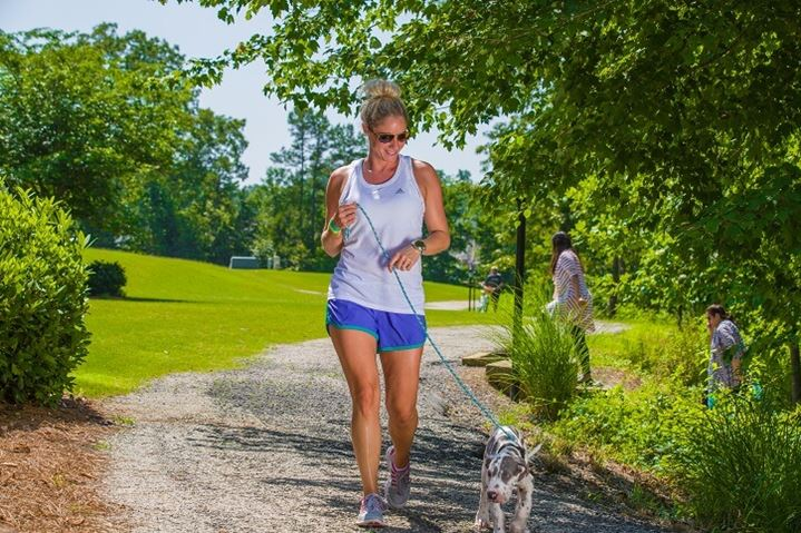 Woman walking puppy on the trails at Sterling on the Lake